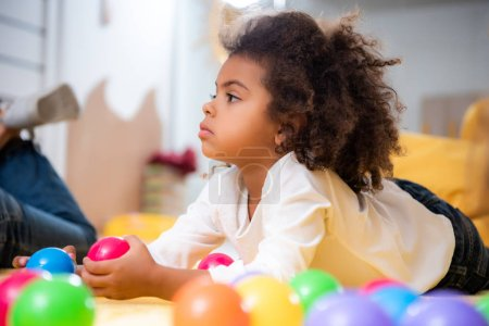 side view of adorable african american kid lying on carpet with toys and looking away in kindergarten