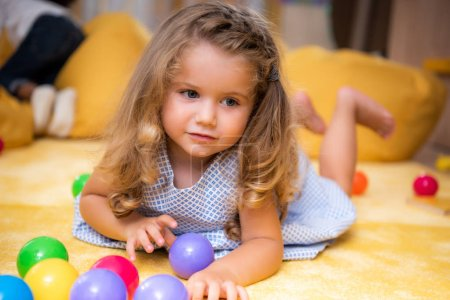 Photo for Adorable caucasian kid lying on carpet with colored balls and looking away in kindergarten - Royalty Free Image