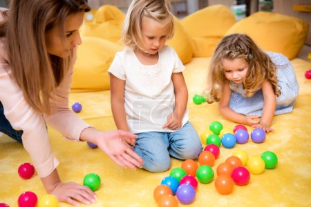 Photo for Educator pointing on colored balls to kids in kindergarten - Royalty Free Image