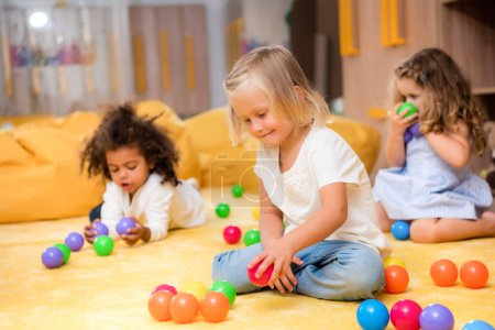 adorable multicultural kids playing with colored balls on floor in kindergarten