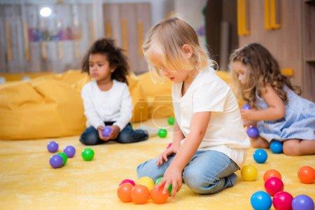 adorable multiethnic children playing with colored balls on floor in kindergarten