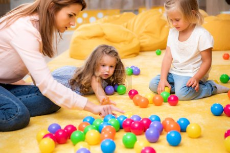 tutor pointing on educational colored balls to kids in kindergarten