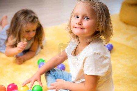adorable cheerful kid taking toys and looking at camera in kindergarten