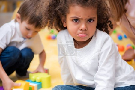 Photo for Dissatisfied african american kid grimacing and looking at camera in kindergarten - Royalty Free Image