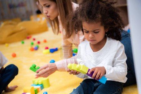 Photo pour Triste enfant africain-américain qui joue avec le constructeur à la maternelle - image libre de droit