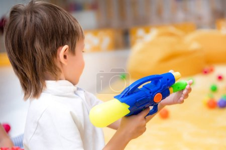 side view of boy playing with water gun in kindergarten