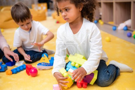 Photo for Upset african american kid taking constructor pieces in kindergarten - Royalty Free Image