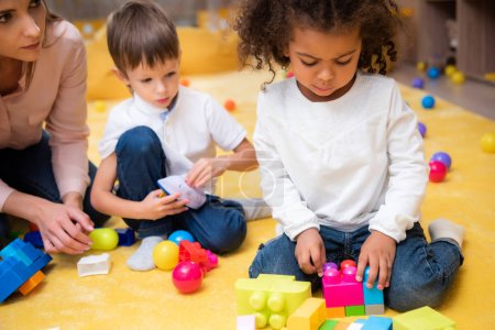 Photo for Upset african american child playing with colored constructor in kindergarten - Royalty Free Image