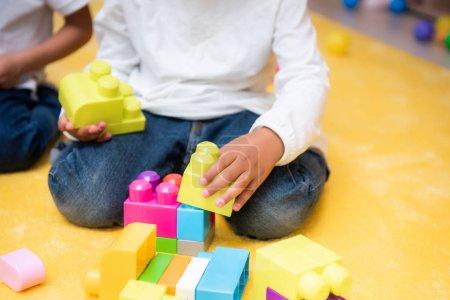 Photo pour Cropped image de l'enfant africain-américain qui joue avec constructeur à la maternelle - image libre de droit