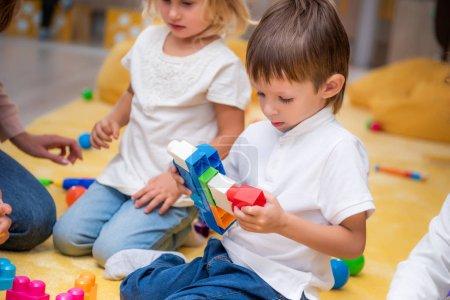 Groupe d'enfants qui jouent avec le constructeur à la maternelle