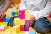 cropped image of african american kid playing with plastic constructor in kindergarten