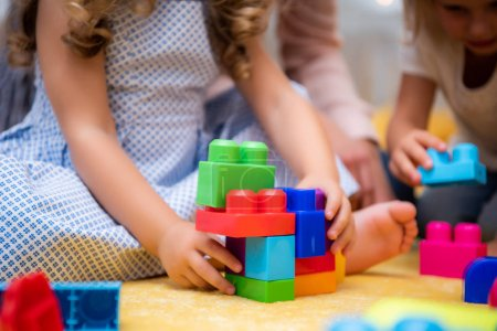 Photo for Cropped image of kids playing with plastic colored constructor in kindergarten - Royalty Free Image