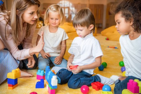 multicultural kids playing with constructor, educator gesturing in kindergarten