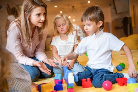 Photo for Educator and caucasian kids playing with constructor in kindergarten - Royalty Free Image