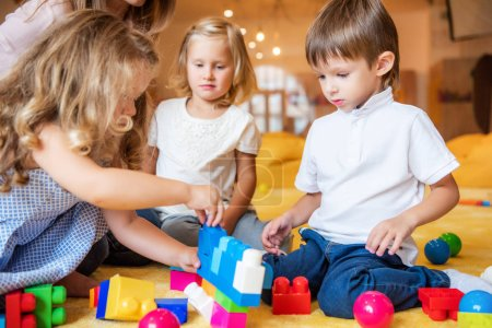 Photo for Adorable kids playing with constructor on floor in kindergarten - Royalty Free Image