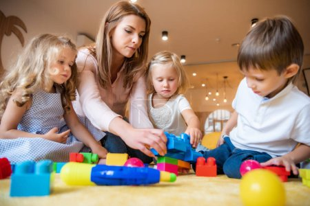 Photo for Educator and adorable kids playing with constructor in kindergarten - Royalty Free Image