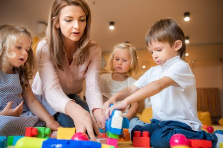 Photo for Educator and kids playing with colored plastic constructor in kindergarten - Royalty Free Image