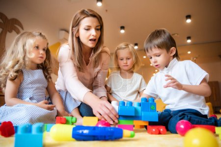 Photo for Caucasian educator helping kids playing with constructor in kindergarten - Royalty Free Image