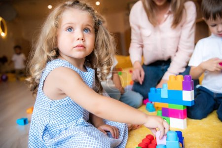 Photo for Adorable kid playing with constructor and looking up in kindergarten - Royalty Free Image