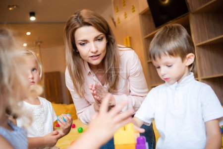 selective focus of educator and kids playing with educational constructor in kindergarten