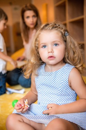 adorable kid holding small toys and looking at camera in kindergarten