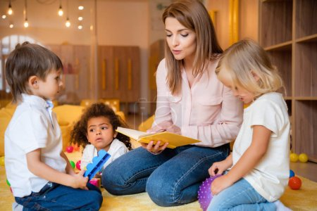tutor reading book for adorable multicultural kids in kindergarten