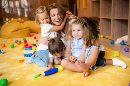 Photo for Laughing educator hugging adorable kids in kindergarten - Royalty Free Image