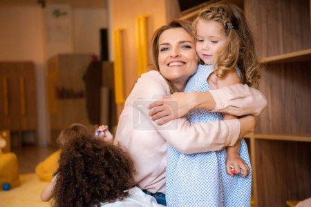 smiling educator cuddling adorable kid in kindergarten