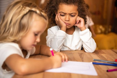 Photo for Dissatisfied african american kid looking at caucasian child drawing at table in kindergarten - Royalty Free Image