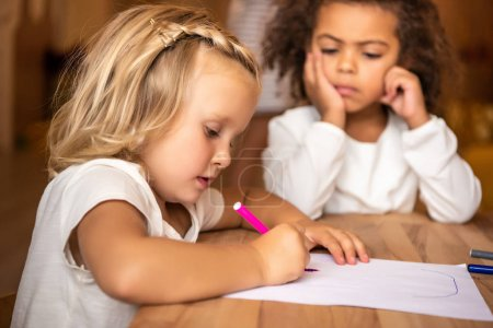 african american kid looking at caucasian child drawing at table in kindergarten