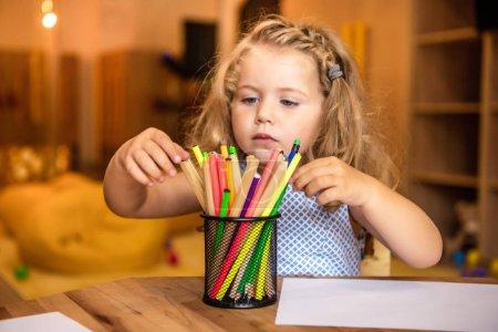 adorable child choosing felt tip pen for drawing in kindergarten