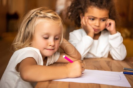 bored african american kid looking away, caucasian child drawing at table in kindergarten