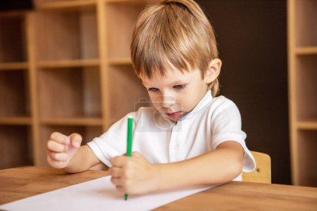 adorable boy drawing with green felt tip pen in kindergarten