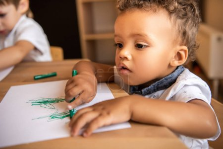 Photo for Adorable african american boy drawing with green felt tip pen in kindergarten - Royalty Free Image