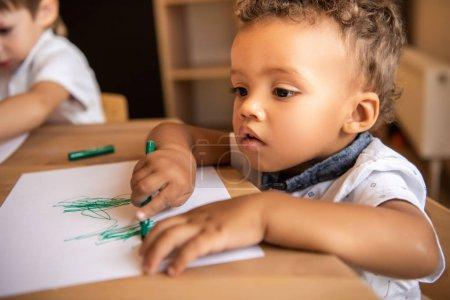 Photo pour Adorable dessin de garçon afro-américain avec stylo feutre vert à la maternelle - image libre de droit