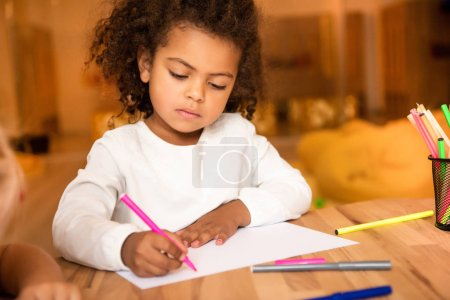 Photo for Adorable african american kid drawing with pink felt pen in kindergarten - Royalty Free Image