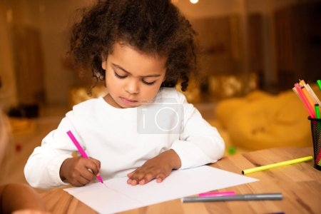Photo for Adorable african american child drawing with pink felt pen in kindergarten - Royalty Free Image