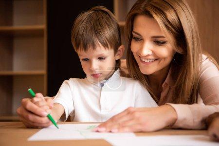 smiling tutor helping boy drawing with green felt pen in kindergarten