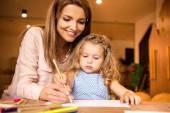 smiling educator helping kid drawing in kindergarten