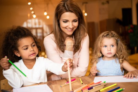 Photo for Cheerful educator sitting near multicultural kids drawing in kindergarten - Royalty Free Image