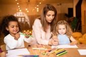 educator helping multicultural kids drawing in kindergarten