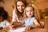 cheerful educator helping adorable kid drawing in kindergarten