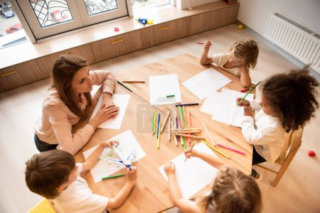 Photo pour Vue grand angle éducateur multiculturel et enfants réunissant à table en maternelle - image libre de droit
