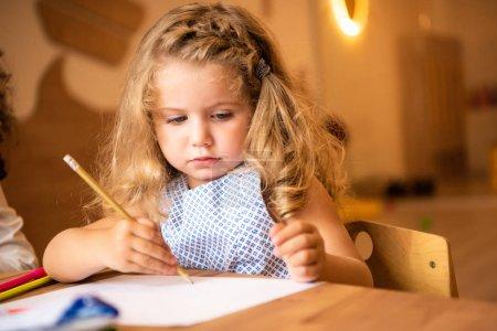 adorable caucasian kid drawing in kindergarten