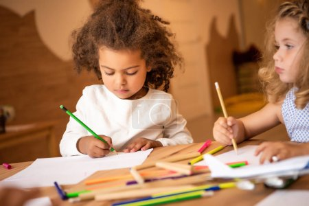 Photo for Adorable multiethnic children drawing with colored pencils in kindergarten - Royalty Free Image