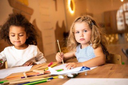multicultural kids drawing with pencils in kindergarten