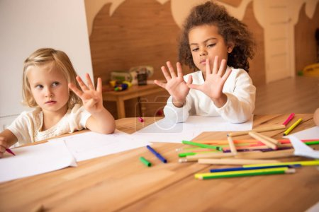 multicultural kids showing numbers with fingers in kindergarten