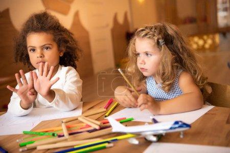 african american kid showing number nine with fingers in kindergarten