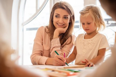 smiling educator and adorable kid drawing together in kindergarten