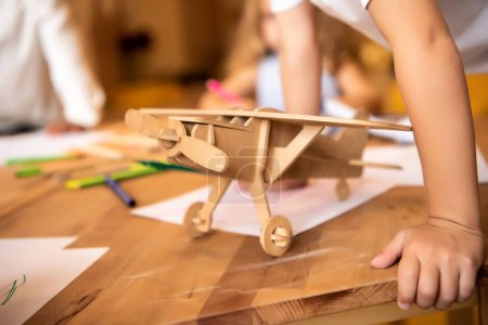 Photo for Children drawing in kindergarten, wooden plane on foreground - Royalty Free Image
